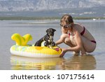 Young woman on the beach playing with dog - stock photo