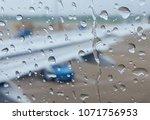 rain drop on the airplane glass ... | Shutterstock . vector #1071756953