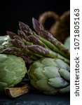 Small photo of A still life of artichokes and asparagus on the rustic textured background close side view low key