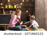 Small photo of Mother teaches son to be kind and friendly. Family play with teddy bear at home. Mom and child play with soft toy. Nursery with chalkboard on background. Kindness and education concept.