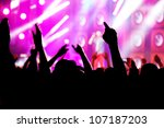 People with hands up having fun on a music concert / disco party. - stock photo