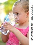 lovely little girl drinking... | Shutterstock . vector #107206163
