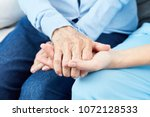 caring nurse or geriatric nurse ... | Shutterstock . vector #1072128533