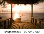 hut by the sea at sunset - stock photo