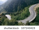 View of curved road running through forest - stock photo