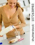 happy young woman pouring milk... | Shutterstock . vector #1072638983