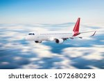 fast airplane over the clouds | Shutterstock . vector #1072680293