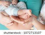 baby feet in parents hands.... | Shutterstock . vector #1072713107