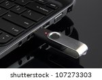 Flash memory drive plugged into a laptop port. - stock photo