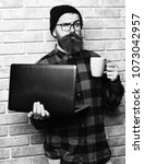 Small photo of Bearded man, long beard. Brutal caucasian serious unshaven hipster holding laptop with mag or cup in red black checkered shirt with hat and glasses on beige brick wall studio background