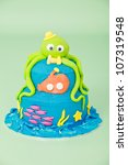 Sea themed birthday party cake with green octopus with hat bow tie and eyes and orange submarine and pink fish on two round blue double tier butter iced cake isolated on a green seamless background - stock photo