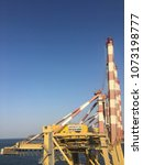 Small photo of Muscat / Oman - 20 April 2018 : Cranes are unloading cargo from ships in the Sultan Qaboos port of Muscat, Oman.