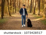 handsome man with a dog walking ... | Shutterstock . vector #1073428517