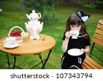 Portrait of elegant child girl in a black dress having a tea party outdoors - stock photo