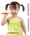 Toddler smiling while brushing her teeth isolated on white - stock photo