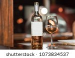 Stock photo bottle of rose wine and glass served with rose wine 1073834537
