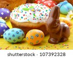 Easter eggs, cake, and bunny shape chocolate - stock photo