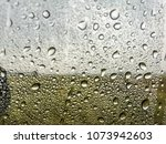 rain falls on a glass of fine... | Shutterstock . vector #1073942603