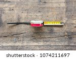 old tape measure against wooden ... | Shutterstock . vector #1074211697