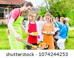happy family having barbeque at ... | Shutterstock . vector #1074244253
