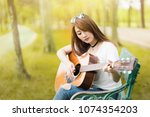 Small photo of Asian teenage girl is practicing guitar. During the summer holidays Playing a musical instrument is a good mental condition.