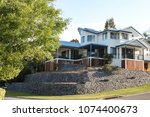 Modern Queenslander house with underporch and lots of outdoor living space - on hill with pretty blue tile roof