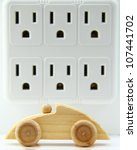 Wooden, toy car in front of a multi-electrical outlet adapter. - stock photo