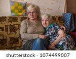 an elderly woman with her adult ... | Shutterstock . vector #1074499007