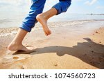 barefoot child running on sandy ...   Shutterstock . vector #1074560723