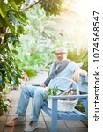 Small photo of Tired senior man sitting on blue wooden bench and having rest in the garden