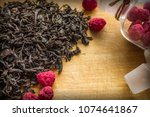 Small photo of Traditional hot drink, aromatic tea with berry additive. Dried raspberries in a glass bottle, homemade billet. Large leaves of black tea on a wooden surface. Daylighting, vignetting.