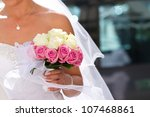 A bride holds her bouquet of pink and wihite roses - stock photo