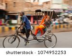 Small photo of Varanasi / India - March 05, 2018. A local rickshaw driver with passenger weaving through the busy streets.