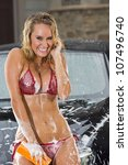 Beautiful bikini models wash a car on a summer day - stock photo