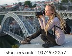 young woman with camera sitting ... | Shutterstock . vector #1074972257