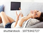 happy woman relaxing at home... | Shutterstock . vector #1075342727