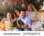 four people enjoy a drink and... | Shutterstock . vector #1075445273