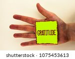 Small photo of Word writing text Gratitude. Business concept for Quality of being thankful Appreciation Thankfulness Acknowledge written on Sticky Note Paper placed on the Hand on the plain background.
