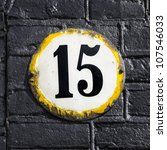 house number fifteen on a round weathered enameled plate - stock photo