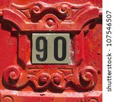 house number ninety surrounded by red ornamentation - stock photo