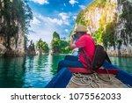 man traveler with backpack joy... | Shutterstock . vector #1075562033