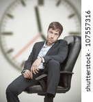 Frustrated young business man waiting for the end of the workday - stock photo