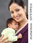 cheerful young mother holding... | Shutterstock . vector #1075709513