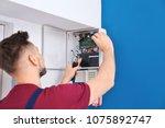 electrician installing alarm... | Shutterstock . vector #1075892747