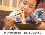 asian girl is eating noodles...   Shutterstock . vector #1076026463