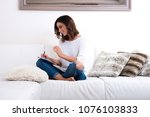 a beautiful young woman siting... | Shutterstock . vector #1076103833
