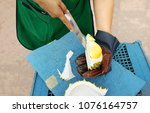 Small photo of Seller making durian by knife and one hand used glove for keep purr peel.