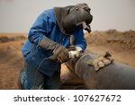 Male welder worker wearing protective clothing fixing welding and grinding industrial construction oil and gas or water plumbing pipeline outside on site - stock photo