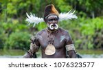 Small photo of Syuru, Asmat Region/ Indonesia - November 9 2012: A chief wears bilas, body ornamentation, appropriate to his station. A pig's tusk nose ornament, and a fur hat decorated with feathers and shells