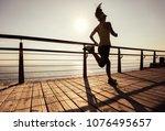 sporty female runner running on ... | Shutterstock . vector #1076495657